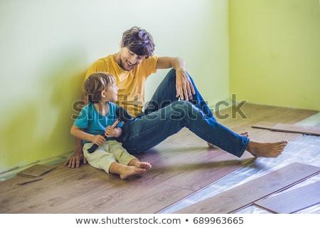 Father and son installing new wooden laminate flooring. infrared floor heating system under laminate Stock photo © galitskaya