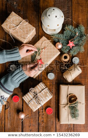 Overview of young woman hands making knot on top of packed and wrapped giftbox Stock photo © pressmaster