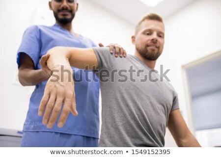 Masseur in blue uniform holding sick arm of patient while massaging it Stock photo © pressmaster