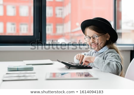Smiling accountant in hat and eyeglasses looking at you while counting salary Stock photo © pressmaster