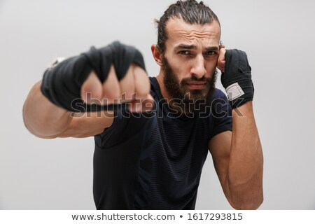 Image of young brutal man in sportswear boxing and looking at camera Stock photo © deandrobot