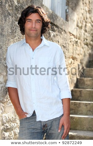 Man abroad leaning against old stone wall Stock photo © photography33
