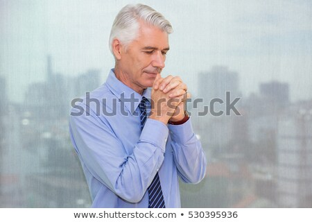 Portrait of matured businessman praying stock photo © stockyimages