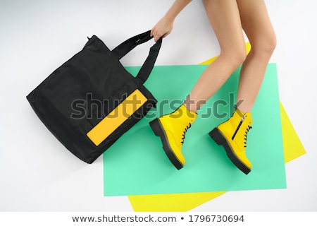 Female legs in bright yellow shoes on a white background Stock photo © pzaxe