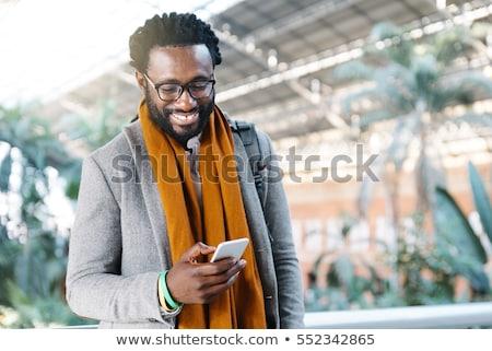 jóképű · afrikai · férfi · mobiltelefon · mosolyog · néz - stock fotó © stockyimages