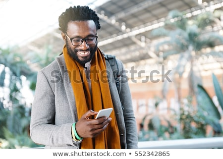 bonito · africano · homem · celular · sorridente · olhando - foto stock © stockyimages