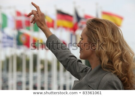 woman hailing a taxi in front of international flags stock photo © photography33