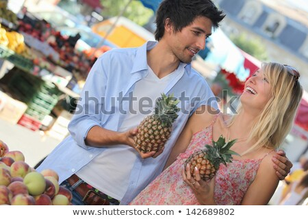 Young couple holding pineapples at a market stall Stock photo © photography33