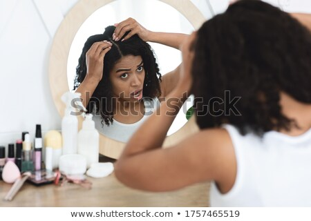 girl looking at her split hair stock photo © rosipro