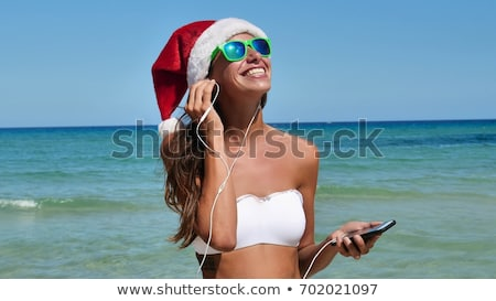 Woman wearing Santa Claus hat and sunglasses listening to music Stock photo © HASLOO
