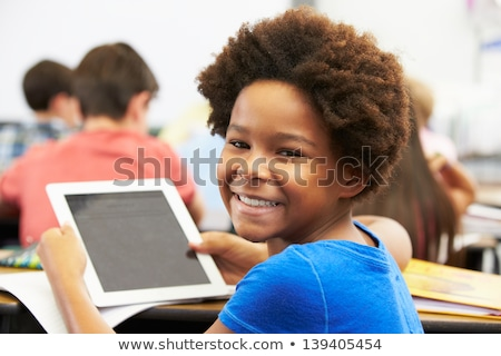 Foto stock: Male Pupil Using Digital Tablet In Classroom