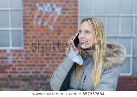 woman chatting on her mobile in front of graffiti stock photo © d13