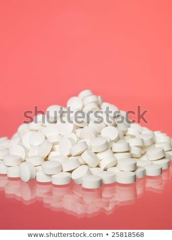 Stack of pills towards red background Stock photo © gemenacom