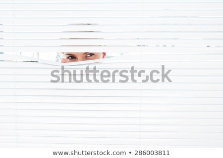 woman observes through blinds Stock photo © ssuaphoto