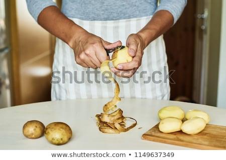 Peeling a potato with peeler on white Stock photo © luissantos84
