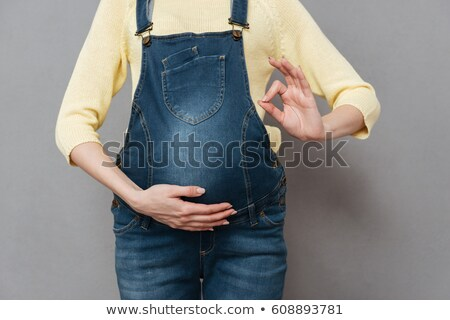Cropped image of pregnant lady make okay gesture. Stock photo © deandrobot