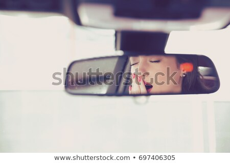rear mirror view of a sleepy yawning woman driving her car after long hour drive stock photo © ichiosea