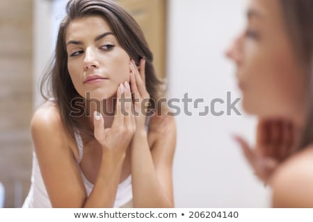 close-up of beautiful woman looking at her reflection Stock photo © julenochek