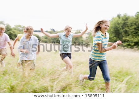 five young friends running outdoors smiling stock photo © monkey_business