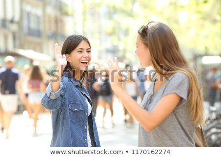 Young cheerful woman walking outdoors waving to friends. Stock photo © deandrobot