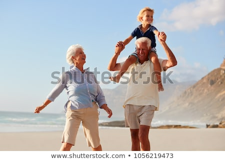 grandparents playing with grandchildren on beach stock photo © is2
