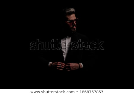 handsome unshaved man wearing black tuxedo looks to side Stock photo © feedough