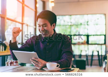 young happy casual man reads sms message on his phone stock photo © feedough