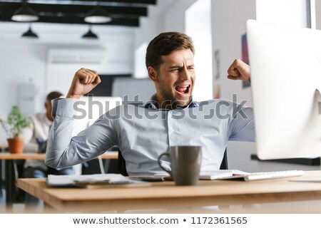 Joyful male manager rejoices while using compute Stock photo © deandrobot