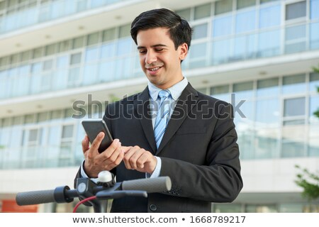 young business man walking outdoors on scooter stock photo © deandrobot