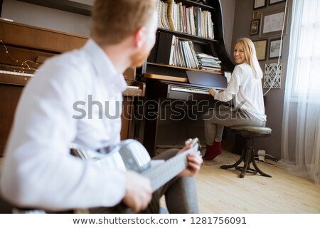 Man playing acoustic guitar with young beautiful woman who plays Stock photo © boggy
