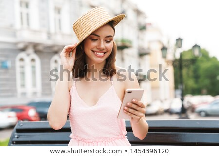 image of pretty woman 20s wearing straw hat smiling while walki stock photo © deandrobot