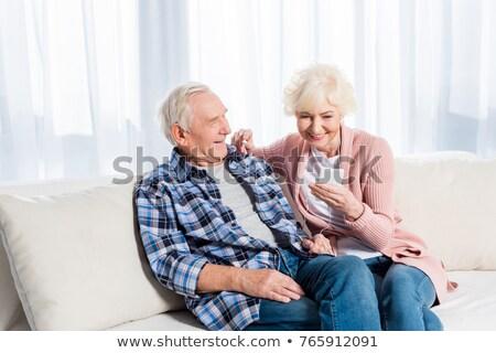 Idős nő okostelefon fülhallgató otthon technológia Stock fotó © dolgachov