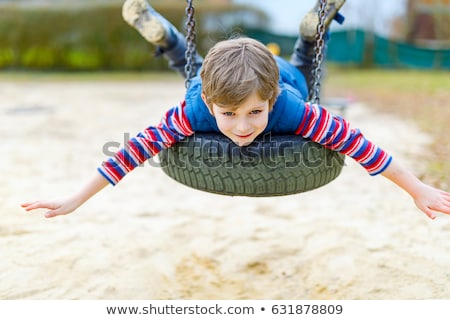 Funny kid boy having fun with chain swing on outdoor playground. child swinging on warm day. Active  Stock photo © galitskaya