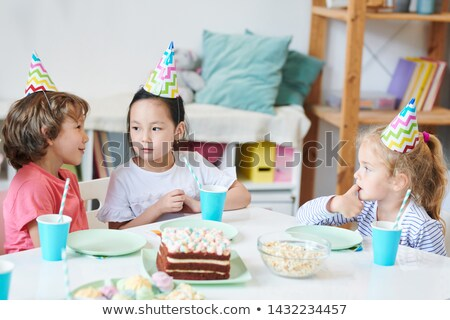 Cute little boy telling something to pretty Asian girl in birthday cap Stock photo © pressmaster