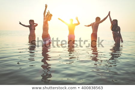 happy friends making high five on beach stock photo © dolgachov