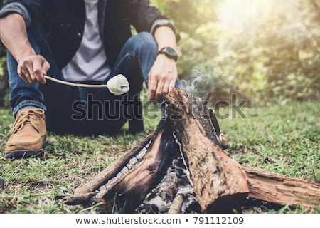 Young Man hiking cooking a marshmallow candies on the campfire i Stock photo © Freedomz