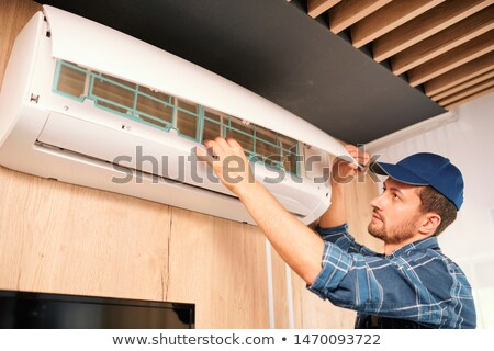 young technician opening lid of air conditioner to check what is wrong with it stock photo © pressmaster