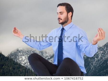Business man meditating against mountains and grey sky Stock photo © wavebreak_media
