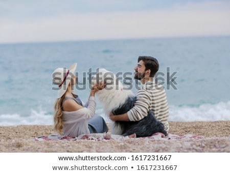 Alternative family with one lady a man and a dog together at the beach enjoying a picnic in friendsh Stock photo © ElenaBatkova