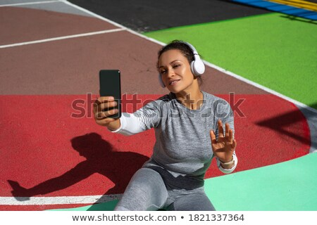 Active healthy woman stretches on floor, wears green tracksuit, makes exercises, has glad expression Stock photo © vkstudio
