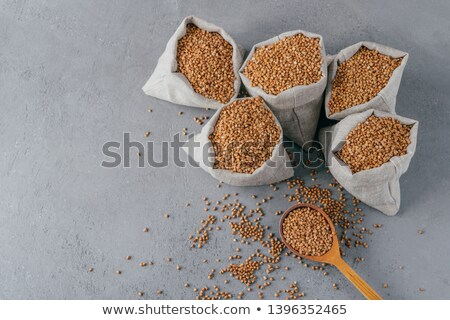 Small sack filled with buckwheat with heap. Important cereal for humans. Top view. Organic product.  Stock photo © vkstudio