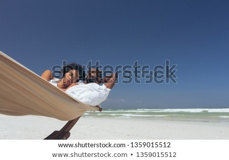 Front view of romantic young multi-ethnic couple relaxing on hammock at beach on sunny day Stock photo © wavebreak_media