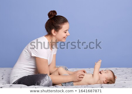 Horizontal shot of cute small daughter sits near her mother who winds curlers, pose against white ba Stock photo © vkstudio