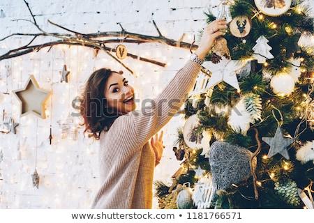 beautiful brunette woman is decorating a christmas tree  Stock photo © juniart