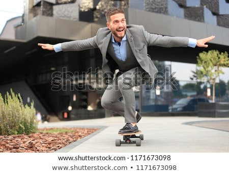Young handsome businessman with longboard in the office  Stock photo © Elnur