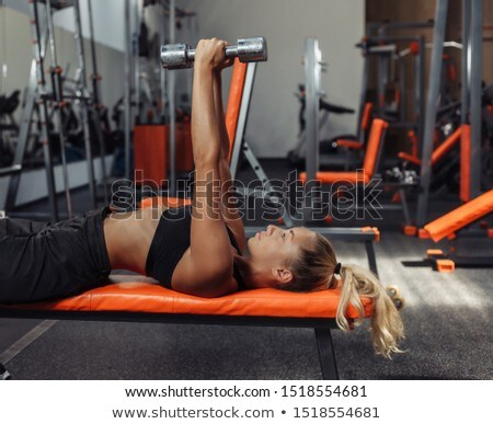 Gym woman fitness training arms lifting free weights. Dumbbell lateral raise shoulder workout Stock photo © Maridav