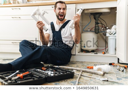 Negative emotional man plumber holding pipe. Stock photo © deandrobot
