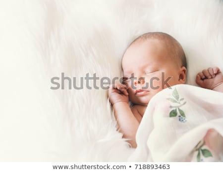 baby girl lying on blanket and mother's hand Stock photo © dolgachov