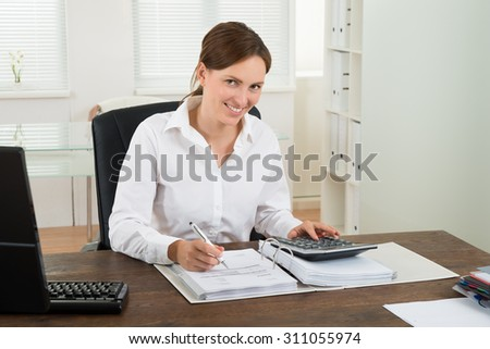 Young Businesswoman Calculating Bill In Office Stock photo © AndreyPopov