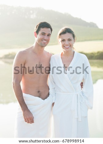 Stock photo: portrait of young couple all smiles wearing bathrobe